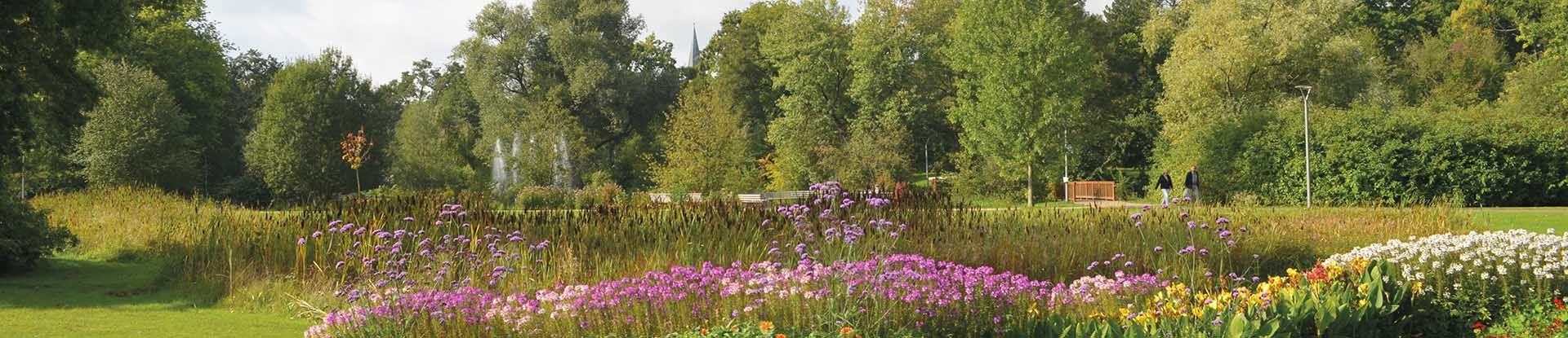 Blühende Blumenbeete im Kurpark mit Blick auf die Dreikönigskirche Bad Bevensen