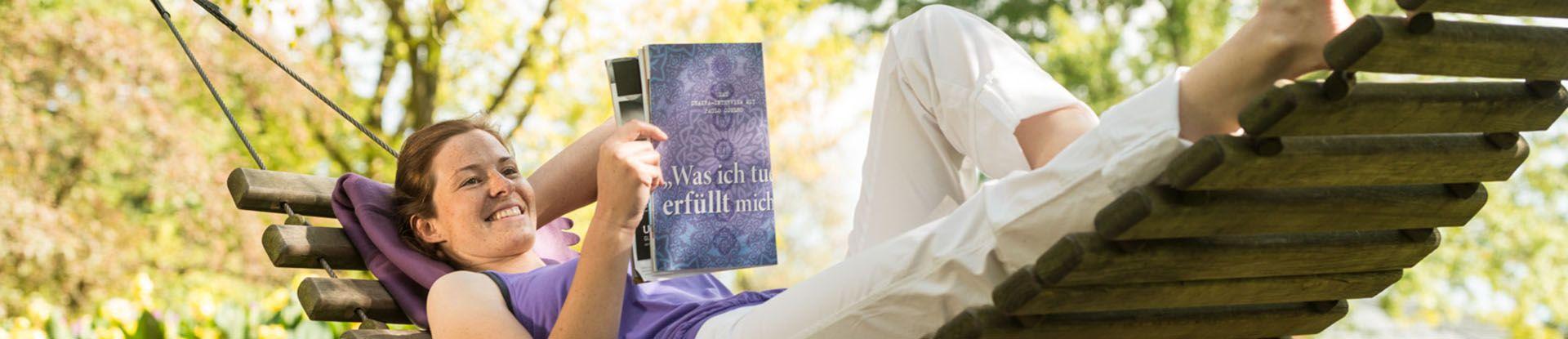 Eine Urlauberin liegt auf einer Hängematte im Kurpark und liest
